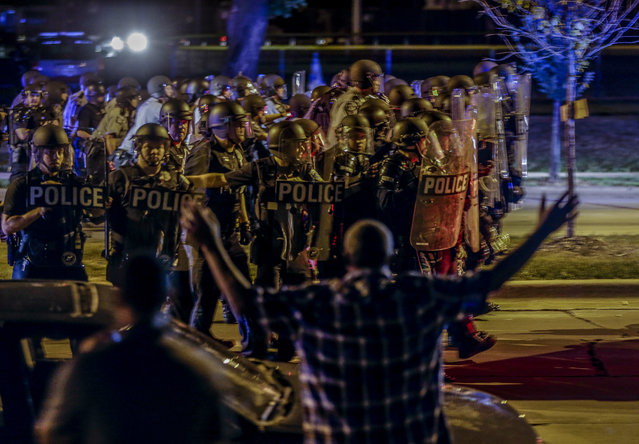 Police move in on a group of protesters throwing rocks at them in Milwaukee, Sunday, August 14, 2016. Police said one person was shot at a Milwaukee protest on Sunday evening and officers used an armored vehicle to retrieve the injured victim during a second night of unrest over the police shooting of a black man, but there was no repeat of widespread destruction of property. (Photo by Jeffrey Phelps/AP Photo)