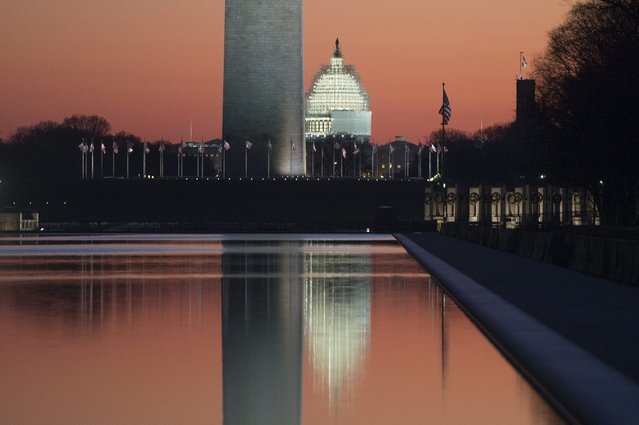 The sun begins to rise on the last day of the year, with the base of the Washington Monument and US Capitol Building reflected in the Lincoln Memorial Reflecting Pool, in Washington DC, USA, 31 December 2014. (Photo by Michael Reynolds/EPA)