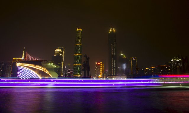 A long exposure picture of boats passing by a business area along the Pearl River in Guangzhou, Guangdong province, in this March 22, 2014 file photo. (Photo by Alex Lee/Reuters)