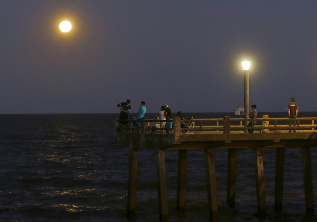 People fish in the waters of the Rio de La Plata as a full moon rises over the Buenos Aires sky December 25, 2015. Its appearance marks the first full moon to happen on Christmas day since 1977, and this phenomenon will not happen again until 2034, according to weather reports. (Photo by Enrique Marcarian/Reuters)