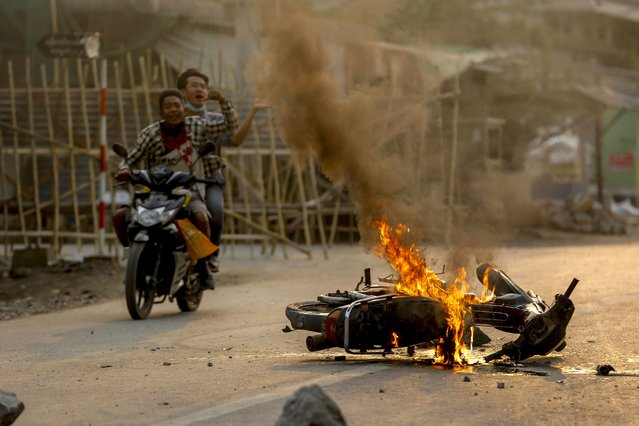 Two men on a motorbike alert people and anti coup protesters as armed security forces arrive to crack down on a demonstration in Mandalay, Myanmar, Tuesday, March 23, 2021. Myanmar's military junta on Tuesday took the offensive to justify last month's coup and subsequent actions against those opposed to it, even as street demonstrations continued against the takeover. (Photo by AP Photo/Stringer)