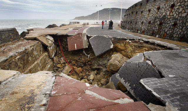 Members of a television crew stand near a hole in the Paseo Nuevo in San Sebastian March 12, 2008. The hole was caused by a storm on Thursday that sunk numerous boats and caused extensive damage in the Biscay area. (Photo by Vincent West/Reuters)