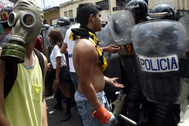 Opposition demonstrators talk to police during a march against President Nicolas Maduro's government in San Cristobal February 12, 2015. (Photo by Carlos Eduardo Ramirez/Reuters)