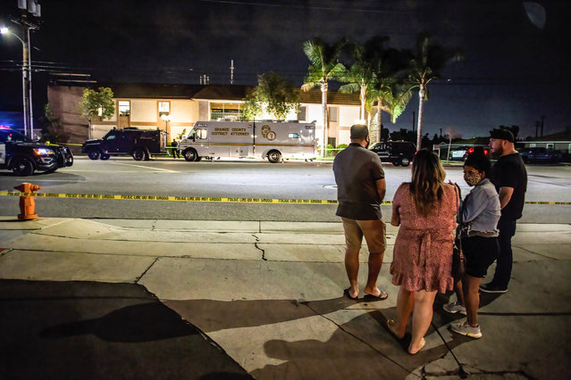 Locals stand and wait for updates across the street from where the shooting occurred on March 31, 2021. On Wednesday evening, four people, including a child, were killed in an office building in Orange, California. The suspect and another person were injured as well. This is the third major shooting in the United States in the last three weeks. (Photo by Stanton Sharpe/SOPA Images/Rex Features/Shutterstock)