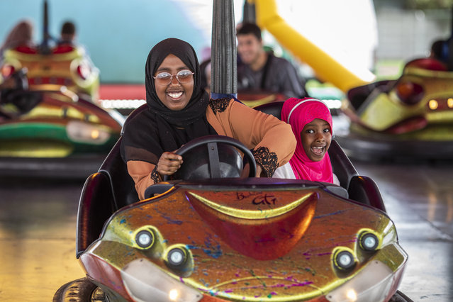 Salma Sulayman, 13, and sister Saabrin Sulayman, 7 enjoy a ride on the dodgems during an Eid in the Park celebration marking Eid Al-Adha at the New River Sports ground in Wood Green on August 21, 2018 in London, England. The traditional four-day celebratory festival marks one of the holiest days in the Islamic religious calendar. (Photo by Dan Kitwood/Getty Images)