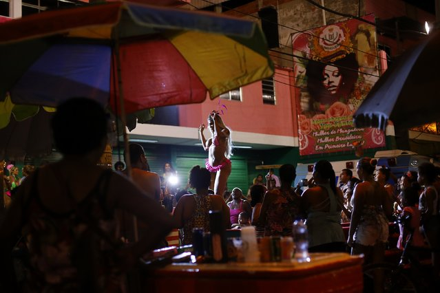 A participant attends a beauty contest for transvestites and transsexuals at the entrance of the Glam Gay pre-carnival Ball, in Mangueira samba school in Rio de Janeiro February 11, 2015. The Rio de Janeiro Carnival will be held from February 13 to 17. (Photo by Ricardo Moraes/Reuters)