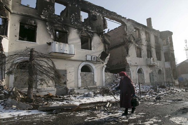A woman walks past a damaged building in the town of Vuhlehirsk near Donetsk, Ukraine, February 14, 2015. (Photo by Baz Ratner/Reuters)