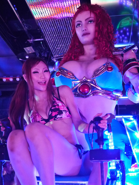 """Bikini-clad women sit as they operate a 3.6 metre-high custom-made female robot as customers take photos, at the """"Robot Restaurant"""" in Kabukicho. (Photo by Tokyo Scum Brigade)"""