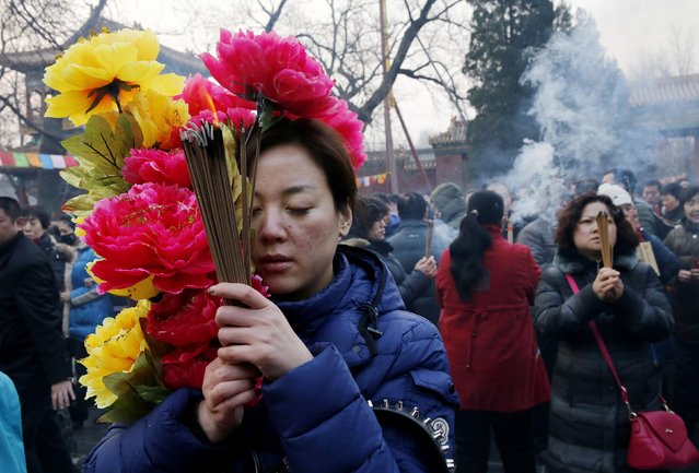 People pray for good fortune as they hold burning incense on the first day of the Chinese Lunar New Year at Yonghegong Lama Temple, in Beijing, February 19, 2015. (Photo by Kim Kyung-Hoon/Reuters)