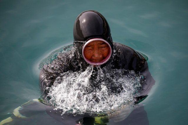 """Kim Myung-soon, a haenyeo, also known as a """"sea woman"""", comes up for air as she dives in the sea off Geoje, South Korea, March 31, 2021. (Photo by Kim Hong-Ji/Reuters)"""
