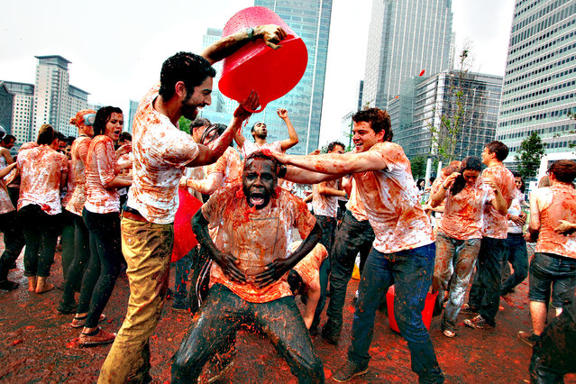 People throw tomatoes during Mission Deli Wraps's re-creation of the famous Spanish tomato-throwing festival, La Tomatina, at Canary Wharf, central London, on September 25, 2013. (Photo by Geoff Caddick/PA Wire)