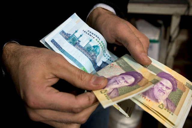 A vendor counts money in a shop in Tehran's Grand Bazaar, Iran, January 19, 2009. (Photo by Raheb Homavandi/Reuters)