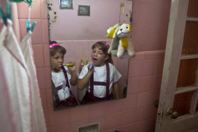 "In this September 23, 2013 photo, six-year-old twin sisters Asley and Aslen Velazquez prepare for school in Havana, Cuba. Their mother Tamara Velazquez said she never expected to have twins from her first pregnancy and did not take fertility treatments. ""It's a lot of work. It requires a lot of patience"", Velazquez said. ""They are very active and dominant, although each has a different character"". (Photo by Ramon Espinosa/AP Photo)"