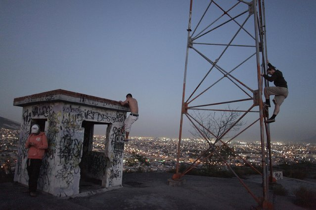 Rory Smith (R), co-founder of Escalando Fronteras (Climbing Borders), climbs a communication tower at the gang-infested neighbourhood of Lomas Modelo, where the group is working with troubled youths, in Monterrey February 4, 2015. According to the group, Climbing Borders aims to empower and help troubled youths in underdeveloped areas around the world through rock-climbing and education, in order to give them the tools to pursue promising and positive lives outside drugs, gangs and organised crime. Since 2014 the group has worked with about 100 youths in the gang-infested neighbourhood of Lomas Modelo in Monterrey. (Photo by Daniel Becerril/Reuters)