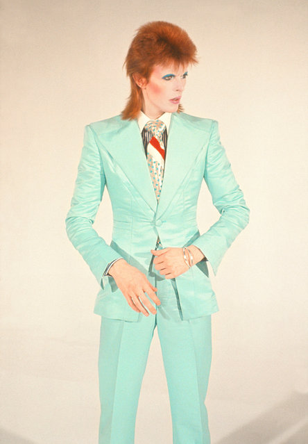 """David Bowie, Life on Mars, 1973 by Mick Rock. """"David Bowie asked me to shoot a video for Life on Mars for its release as a single. I photographed him in the Freddie Burretti suit he wore for it with makeup by Pierre La Roche (who had styled him for the cover of Aladdin Sane). He never wore that suit again, never had that makeup on again. He never looked more amazing – like a space doll. A couple of months later he famously retired the androgynous Ziggy Stardust character, after which he started wearing a lot of tailored suits. This photograph catches him morphing from one look to another"""". (Photo by Mick Rock/Rock Sale2018)"""