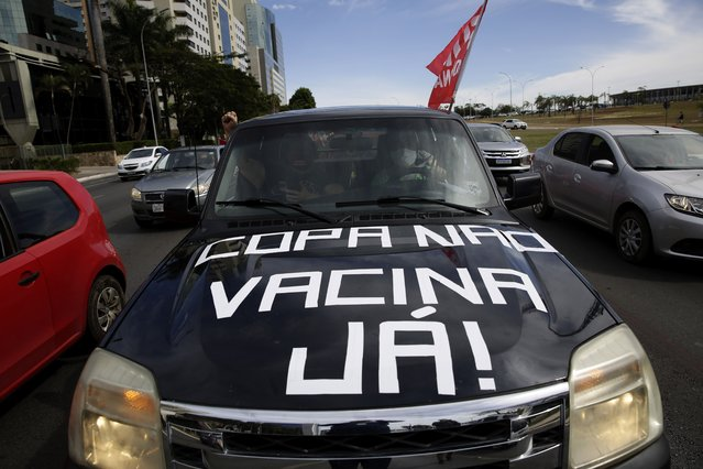 """Protesters drive their car with a sign reading in Portuguese """"Copa No, Vaccines Now"""" to protest the holding of Copa America in Brasilia, Brazil, Sunday, June 6, 2021. Brazil accepted hosting the South American soccer tournament after the original co-hosts were dropped: Colombia due to political protests and Argentina for rising of COVID-19 cases. (Photo by Eraldo Peres/AP Photo)"""
