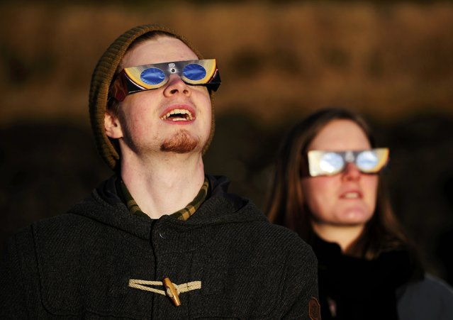 People wearing solar viewing glasses observe a partial solar elcipse in Reykjavik March 20, 2015. (Photo by Sigtryggur Ari/Reuters)