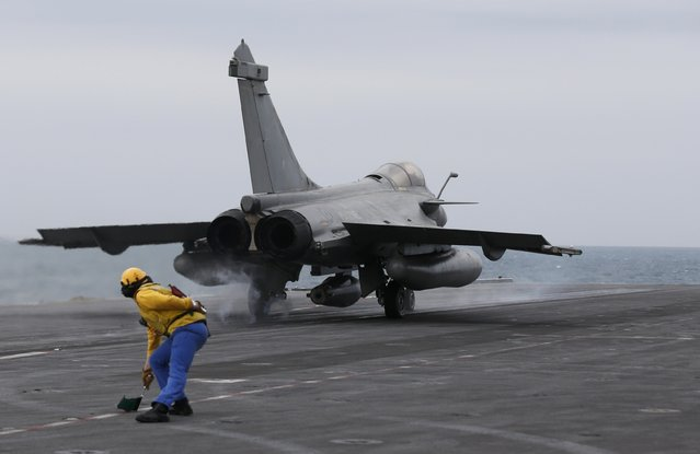 A yellow dog deck officer signals as a Rafale fighter jet takes off from France's Charles de Gaulle aircraft carrier in the Gulf, January 27, 2016. (Photo by Philippe Wojazer/Reuters)