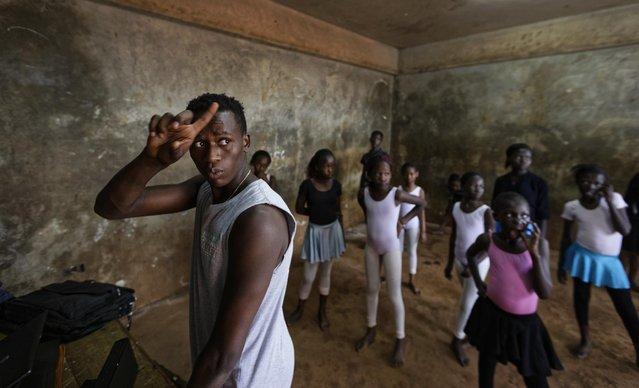 In this photo taken Friday, December 9, 2016, young ballerinas practice under the instruction of Kenyan ballet dancer Joel Kioko, 16, left, in a room at a school in the Kibera slum of Nairobi, Kenya. (Photo by Ben Curtis/AP Photo)