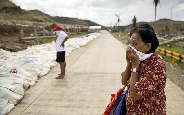 """A woman covers her nose and mouth as she stopped to look at the body bags containing the remains of some 170 dead collected from the rubble at the """"Cemetery of the hills"""", one of three mass burial sites where they so far have received one thousand typhoon victims in Tacloban on November 19, 2013. Philippine President Benigno Aquino blamed the slow response to the ravages of Typhoon Haiyan on the total collapse of local government in the face of the storm's unprecedented destructive power. (Photo by Odd Andersen/AFP Photo)"""