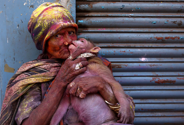 A woman daubed in colours kisses her monkey during Holi celebrations in Chennai, India, March 2, 2018. (Photo by P. Ravikumar/Reuters)