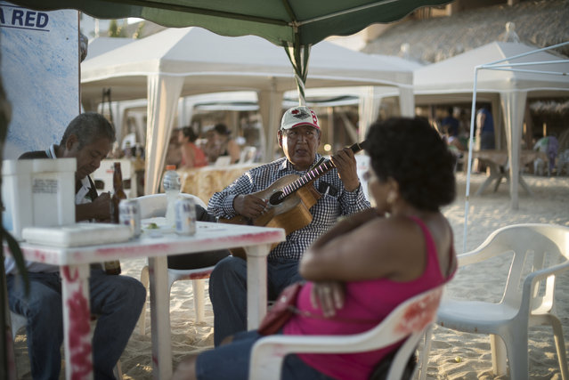A man plays music for his friends on April 1, 2015 in Acapulco, Mexico. (Photo by Jonathan Levinson/The Washington Post)