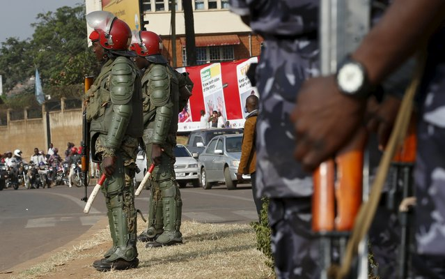 Military personnel hold their weapons as they watch a procession by Uganda's leading opposition party Forum for Democratic Change supporters being dispersed in Kampala, Uganda, February 15, 2016. (Photo by James Akena/Reuters)