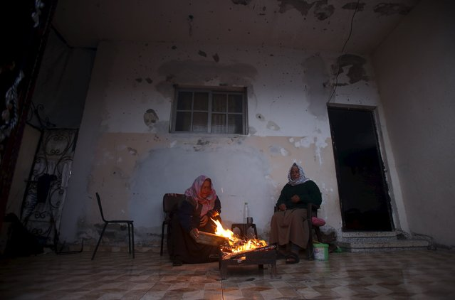 An elderly Palestinian man and his wife warm themselves by a fire inside their house damaged during 2014 war, on a stormy day in Beit Hanoun in the northern Gaza Strip February 7, 2016. (Photo by Suhaib Salem/Reuters)