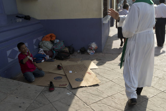 Carlos Titoto, a priest with Scalabrinian Missionaries, blesses a young Central American migrant sitting outside a Catholic church in Tecun Uman, Guatemala on the border with Mexico, Sunday, January 20, 2019. The migratory trail north from Mexico and the violent Northern Triangle region of Central America is fraught with peril, where along the way, migrants rely on a network of support in the form of Catholic-run shelters where they can find a place to sleep, be safe from the cartels and get a meal or advice. (Photo by Moises Castillo/AP Photo)
