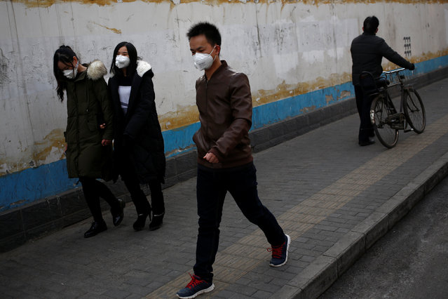 People wear masks on a hazy day in Beijing, China, December 31, 2016. (Photo by Thomas Peter/Reuters)