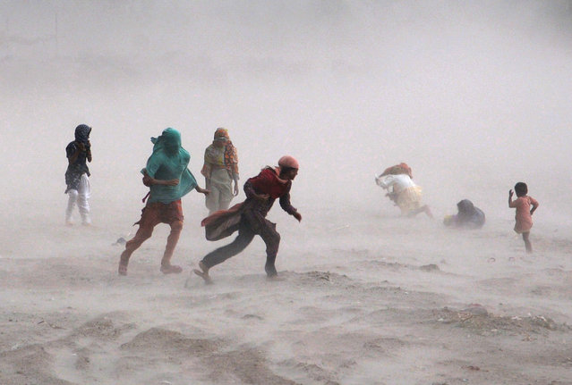 Pakistani people walk through a storm near the Ravi river in Lahore on September 15, 2013. (Photo by Arif Ali/AFP Photo)