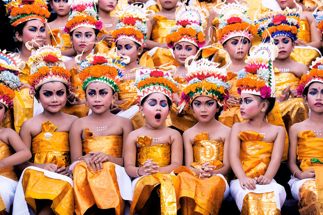 """Khairel Anuar Che Ani, Malaysia. Open Competition; Split Second. Young girls wait for their turn to perform during the Melasti festival: """"They looked stunning with their bright costumes and heavy make-up; however the expression on each of the girls' faces – especially the yawning girl – gives this image extra oomph"""". (Photo by Khairel Anuar Che Ani/Sony World Photography Awards)"""
