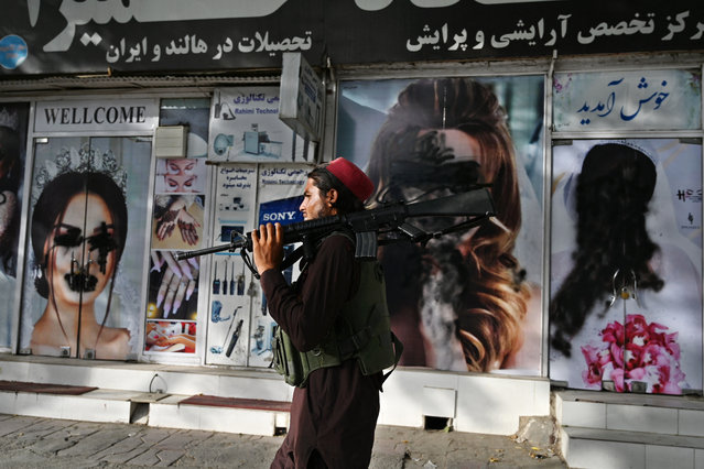 A Taliban fighter walks past a beauty salon with images of women defaced using spray paint in Shar-e-Naw in Kabul on August 18, 2021. (Photo by Wakil Kohsar/AFP Photo)