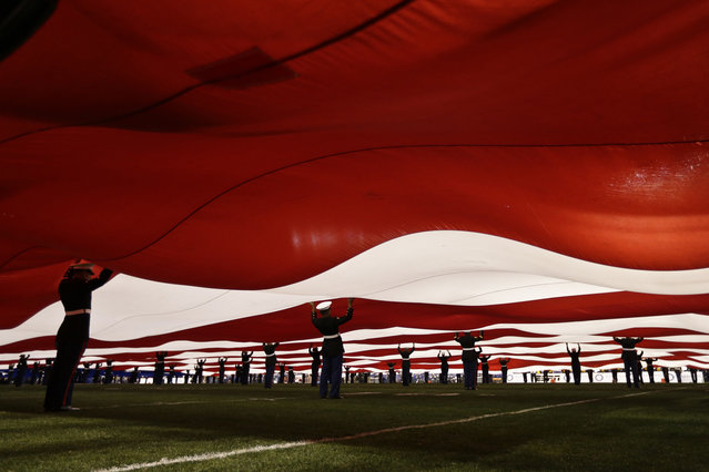United States Marines support a 100 yard American flag during pre-game ceremonies at the Holiday Bowl NCAA college football game Monday, December 30, 2013, in San Diego. (Photo by Gregory Bull/AP Photo)