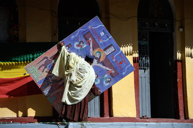 A priest carries a picture of Christ on the cross as final preparations are made as Timkat celebrations get under way on January 18, 2017 in Gondar, Ethiopia. Timkat is the Ethiopian Orthodox Christian festival which celebrates the baptism of Jesus in the Jordan river. During the festival, Tabots, or models of the Ark of the Covenant, are taken from churches around Gondar and paraded through the streets to Fasilides Bath. (Photo by Carl Court/Getty Images)
