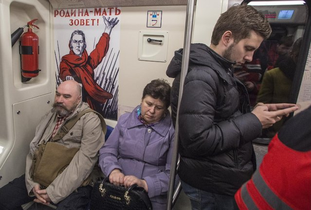 "Passengers ride a subway train decorated with a famous World War II era poster reading ""Motherland calls!"" in Moscow, Russia, Wednesday, April 22, 2015. Russia will celebrate the 70th anniversary of the Victory in WWII on May 9, 2015. (Photo by Denis Tyrin/AP Photo)"