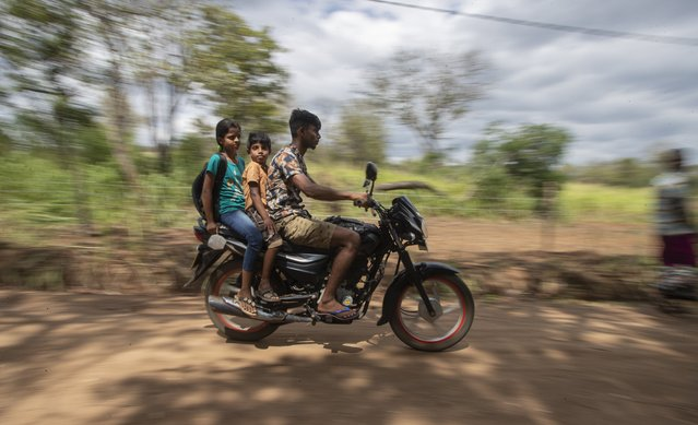 Sri Lankan students ride a motorbike back home after attending their online classes from a nearby mountain top in Bohitiyawa village in Meegahakiwula, Sri Lanka, July 2, 2021. Climbing rocks and sitting on tree tops is not part of their curriculum but children in villages surrounding the capital city are doing just that to be able to catch mobile signals to access their online classes. The digital divide fueled by uneven internet access and high data cost has forced many students out of the formal education system in Sri Lanka. (Photo by Eranga Jayawardena/AP Photo)