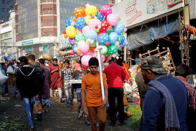 A boy carries balloons for sale in the streets of Dhaka Bangladesh, January 25, 2017. (Photo by Mohammad Ponir Hossain/Reuters)