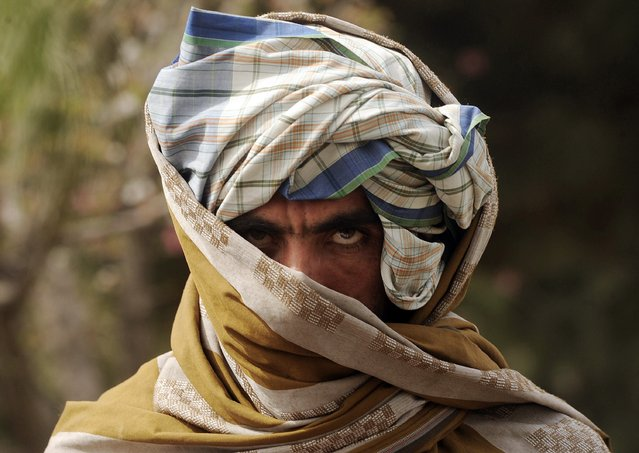 A former Taliban fighter looks on after joining Afghan government forces during a ceremony in Herat province on March 26, 2012. (Photo by Aref Karimi/AFP Photo)
