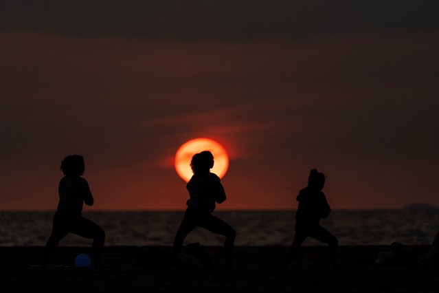 People perform yoga poses on the beach as the sun goes down over the horizon, Tuesday, September 28, 2021, in Santa Monica, Calif. (Photo by Jae C. Hong/AP Photo)