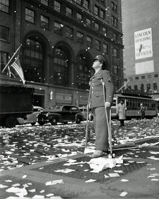 Staff Sgt. Arthur Moore of Buffalo, N.Y., who was wounded in Belgium, stands on 42nd Street near Grand Central Station in New York Monday, May 7, 1945 as New Yorkers celebrate news of VE Day, victory over Nazi Germany. (Photo by AP Photo)