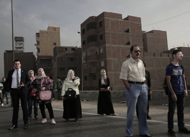 In this October 23, 2018 photo, people wait for an early morning bus on the ring road, in Cairo, Egypt. A city of 20 million people that combines charm and squalor, Cairo may soon witness an exodus by some of its well-heeled residents, state employees and foreign embassies to a new capital. The government argues that Cairo is already bursting at the seams and will grow to 40 million by 2050. (Photo by Nariman El-Mofty/AP Photo)