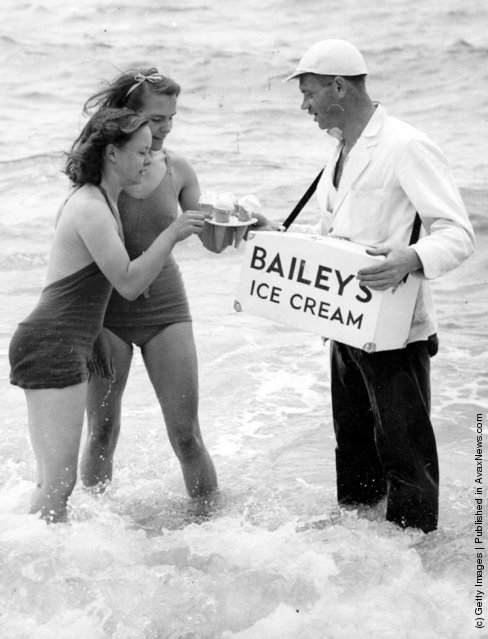 An ice cream vendor wearing waders sells Bailey's ice cream to two women bathing in the sea at Brighton, 1939