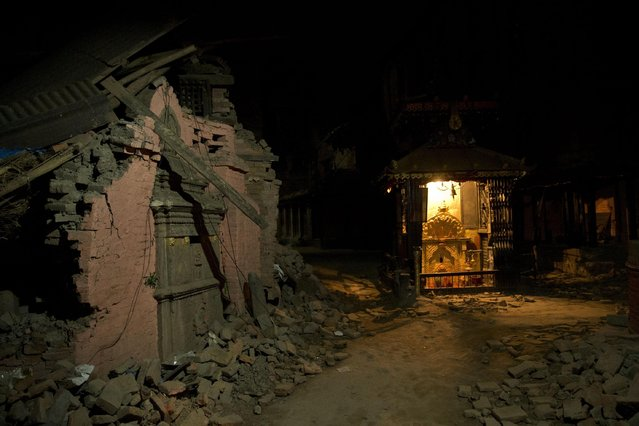 A temple, right, in an area that was damaged a week ago during the earthquake in Bhaktapur, Nepal, Sunday, May 3, 2015. The true extent of the damage from the April 25 earthquake is still unknown as reports keep filtering in from remote areas, some of which remain entirely cut off. The U.N. says the quake affected 8.1 million people – more than a quarter of Nepal's 28 million people. (Photo by Bernat Amangue/AP Photo)