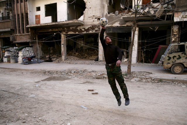 A Free Syrian Army fighter plays with a ball in the rebel-controlled area of Jobar, a suburb of Damascus, Syria March 23, 2016. (Photo by Bassam Khabieh/Reuters)