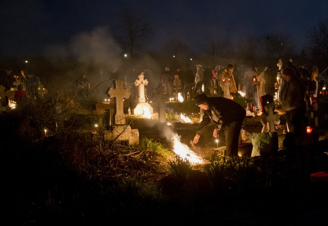 People stand by fires they lit by a relative's grave in a cemetery during an Orthodox Palm Sunday memorial for the departed in Herasti, southern Romania, early Sunday, April 5, 2015. Orthodox believers gather at midnight, light fires at the graves and share food in memory of their dead relatives. (Photo by Vadim Ghirda/AP Photo)