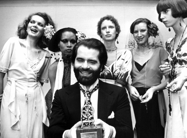 In this November 29, 1973 photo German fashion designer Karl Lagerfeld, left, poses with models in Krefeld, Germany. Chanel's iconic couturier, Karl Lagerfeld, whose accomplished designs as well as trademark white ponytail, high starched collars and dark enigmatic glasses dominated high fashion for the last 50 years, has died. He was around 85 years old. (Photo by Willi Bertram/dpa via AP Photo)