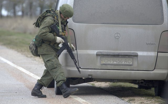 An unidentified gunman searches a vehicle while he and others block the road toward the military airport at the Black Sea port of Sevastopol in Crimea, Ukraine, Friday, Feb. 28, 2014. (Photo by Ivan Sekretarev/AP Photo)