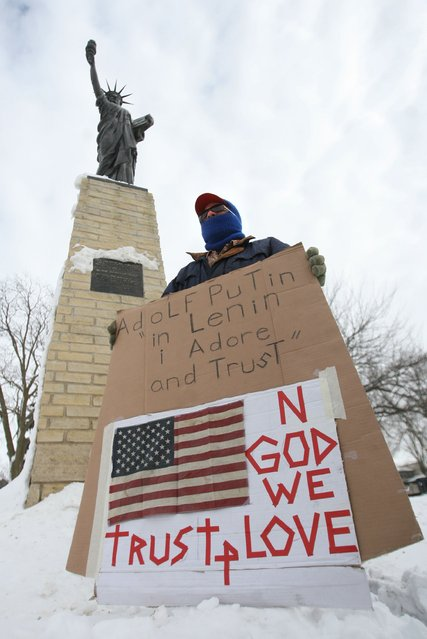 A man protests the situation in Ukraine next to a replica of the Statue of Liberty in Mason City, Iowa, Monday, March 3, 2014. The man who refused to be identified wanted to join other protesters around the world. (Photo by Arian Schuessler/AP Photo/The Globe Gazette)