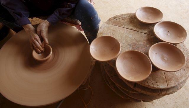 A woman makes clay lids at a factory at Phu Lang pottery village in Bac Ninh province, Vietnam, May 14, 2015. (Photo by Reuters/Kham)